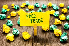 Writing note showing Free Trade. Business photo showcasing The ability to buy and sell on your own terms and means Clothespin hold. Ing yellow note paper royalty free stock photos