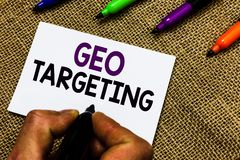 Writing note showing Geo Targeting. Business photo showcasing Digital Ads Views IP Address Adwords Campaigns Location Man hand hol. Ding marker white paper royalty free stock photo
