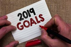 Writing note showing 2019 Goals. Business photo showcasing A plan to do for something new and better for the coming year Man's ha. Nd hold white paper with royalty free stock photography