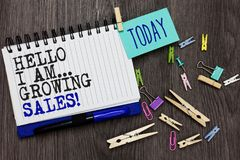 Writing note showing Hello I Am... Growing Sales. Business photo showcasing Making more money Selling larger quantities Different. Paperclip on woody table stock photography