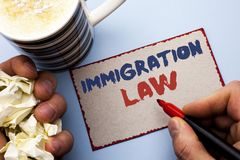 Writing note showing Immigration Law. Business photo showcasing National Regulations for immigrants Deportation rules written by. Man Cardboard Piece Holding stock photography