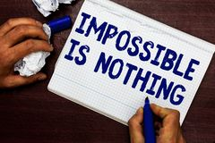 Writing note showing Impossible Is Nothing. Business photo showcasing Anything is Possible Believe the Realm of. Possibility Man holding marker notebook page royalty free stock images
