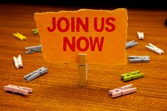 Writing note showing Join Us Now. Business photo showcasing enroll community register website Recruit someone Sign-up Paperclip h. Olding orange page show red stock images