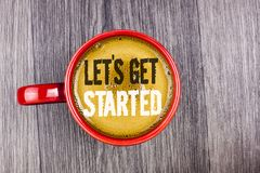 Writing note showing Lets Get Started. Business photo showcasing beginning time motivational quote Inspiration encourage written. Coffee in Red Cup the Grey royalty free stock image