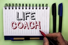 Writing note showing  Life Coach. Business photo showcasing Mentoring Guiding Career Guidance Encourage Trainer Mentor written by. Man Holding Marker Nootbook Royalty Free Stock Photography