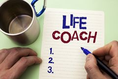 Writing note showing  Life Coach. Business photo showcasing Mentoring Guiding Career Guidance Encourage Trainer Mentor written by. Man Notebook Paper Holding Stock Photos