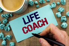 Writing note showing  Life Coach. Business photo showcasing Mentoring Guiding Career Guidance Encourage Trainer Mentor written by. Man Holding Pen Sticky Note Stock Photography