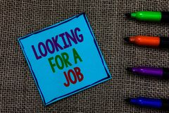 Writing note showing Looking For A Job. Business photo showcasing Unemployed seeking work Recruitment Human Resources Blue paper o. N written letters besides royalty free stock image