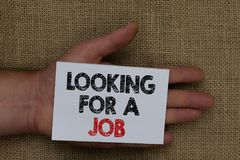 Writing note showing Looking For A Job. Business photo showcasing Unemployed seeking work Recruitment Human Resources Human hand h. Olding white page with black royalty free stock image
