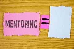 Writing note showing  Mentoring. Business photo showcasing To give advice or support to a younger less experienced person written. Tear Sticky note paper wooden Royalty Free Stock Photo