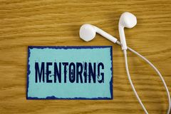 Writing note showing  Mentoring. Business photo showcasing To give advice or support to a younger less experienced person written. Sticky Note Paper wooden stock image