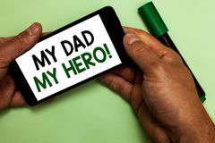 Writing note showing My Dad My Hero. Business photo showcasing Admiration for your father love feelings emotions compliment Human. Hand hold phone with texts royalty free stock photo