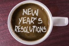 Writing note showing  New Year\'S Resolutions. Business photo showcasing Goals Objectives Targets Decisions for next 365 days writ. Ten Coffee in White Cup the Royalty Free Stock Photos
