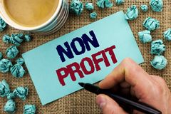 Writing note showing Non Profit. Business photo showcasing Charitable Wrothless Philanthropy Aid Unlucrative Profitless written b. Y Man Holding Pen Sticky Note royalty free stock images