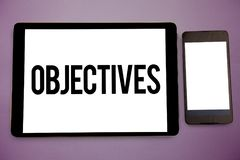 Writing note showing Objectives. Business photo showcasing Goals planned to be achieved Desired targets Company missions Wide fram. Ed white smart screen tablet royalty free stock image