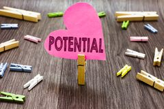 Writing note showing Potential. Business photo showcasing Latent qualities abilities capacity to develop in the future Clothespin. Holding pink paper heart royalty free stock photography