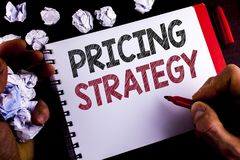 Writing note showing  Pricing Strategy. Business photo showcasing Marketing sales strategies profit promotion campaign written by. Man Notepad holding Marker Stock Photo