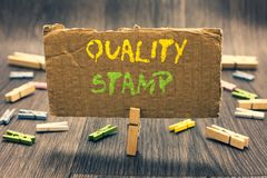 Writing note showing Quality Stamp. Business photo showcasing Seal of Approval Good Impression Qualified Passed Inspection Clothes. Pin holding paperboard stock photo
