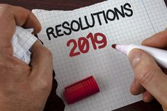 Writing note showing  Resolutions 2019. Business photo showcasing Positive reinforcement personal improvent corporate goals writte. N by Man Tear Notebook paper Stock Photos