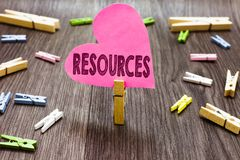 Writing note showing Resources. Business photo showcasing Money Materials Staff and other assets needed to run a company. Clothespin holding pink paper heart stock photography