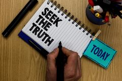 Writing note showing Seek The Truth. Business photo showcasing Looking for the real facts Investigate study discover Man holding m. Arker notebook clothespin royalty free stock photo