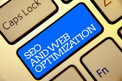 Writing note showing Seo And Web Optimization. Business photo showcasing Search Engine Keywording Marketing Strategies Golden colo. R computer keyboard blue royalty free stock photo