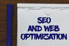 Writing note showing Seo And Web Optimization. Business photo showcasing Search Engine Keywording Marketing Strategies Written whi. Te notepad on grey wooden stock images