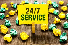 Writing note showing 24 7 Service. Business photo showcasing Always available to serve Runs constantly without disruption Clothesp. In holding yellow note paper royalty free stock photos