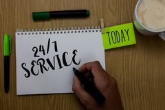 Writing note showing 24 7 Service. Business photo showcasing Always available to serve Runs constantly without disruption Man hold. Ing marker notebook clothepin stock photography