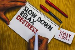 Writing note showing Slow Down Relax Destress. Business photo showcasing calming bring happiness and put you in good mood Man hold. Ing marker notebook clothepin Stock Images