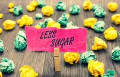 Writing note showing Less Sugar. Business photo showcasing Lower volume of sweetness in any food or drink that we eat Clothespin h. Olding pink note paper Stock Photography