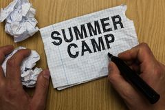Writing note showing Summer Camp. Business photo showcasing Supervised program for kids and teenagers during summertime. Man holdi. Ng marker notebook paper royalty free stock image
