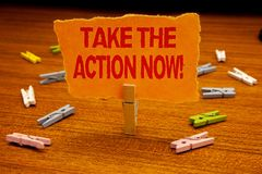 Writing note showing Take The Action Now Motivational Call. Business photo showcasing Act Start Promptly Immediate Instantly Pape. Rclip holding orange page show royalty free stock photos