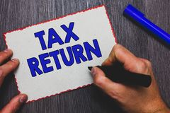 Writing note showing Tax Return. Business photo showcasing which taxpayer makes annual statement of income circumstances Man holdi. Ng marker paper red borders royalty free stock image