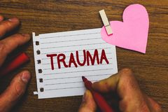 Writing note showing Trauma. Business photo showcasing Disturbing physical and emotional injuries shock experience Small pitch pap. Er clip paperclip love wood stock photo