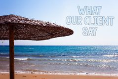 Writing note showing What Our Client Say. Business photo showcasing Customers Feedback or opinion about product service Blue beac. H sand message idea sunshade Royalty Free Stock Images