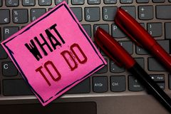 Writing note showing What To Do. Business photo showcasing asking someone advice about next action is going to be made Pink paper. Keyboard Inspiration stock photo