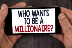 Writing note showing  who Wants To Be A Millionaire Question. Business photo showcasing Earn more money applying knowledge written. Mobile Phone Screen holding Stock Images