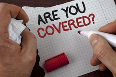 Writing note showing  Are You Covered Question. Business photo showcasing Health insurance coverage disaster recovery written by M. An Tear Notebook paper wooden Royalty Free Stock Photo