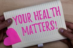 Writing note showing Your Health Matters. Business photo showcasing Physical Wellness is Important Stay Fit and Healthy. Man holding notebook paper heart royalty free stock photography