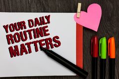 Writing note showing Your Daily Routine Matters.. Business photo showcasing Have good habits to live a healthy life Bold red words. Pen on page small heart royalty free stock photography