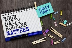 Writing note showing Your Daily Routine Matters.. Business photo showcasing Have good habits to live a healthy life Different pape. Rclip on woody table pinch on royalty free stock photography