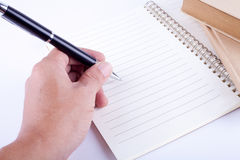 Writing on the notebook. Hand writing with a pen Royalty Free Stock Photo