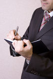 Writing in notebook. A businessman writes in the black working notebook royalty free stock images