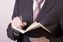 Writing in notebook. A businessman writes in the black working notebook royalty free stock photos