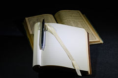 Writing notebook with pen on vintage textbook. Writing and notes on paper with pen with vintage textbook in background Stock Photography