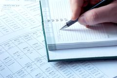 Writing in notebook tax help. Male hand writing in the agenda tax help Royalty Free Stock Photography