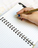 Writing on notepad. A woman's hand getting ready to write on a blank notepad page, writing and note taking concept Stock Image
