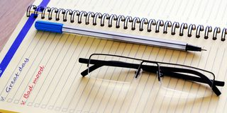 The writing in Notepad. Great day without a bad mood. A detailed notebook and glasses. For work stock photos