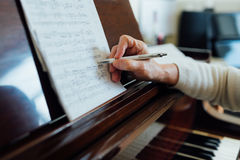 Writing notes on sheet music Royalty Free Stock Photos